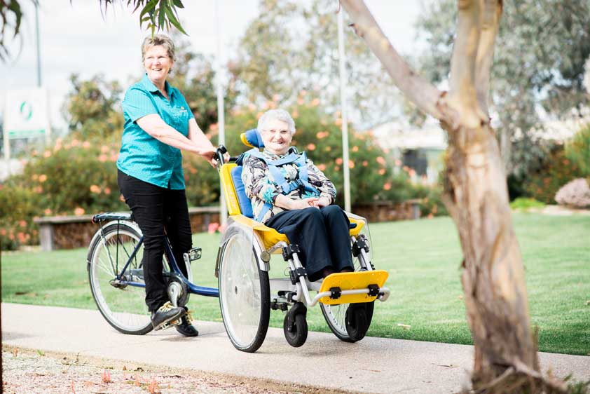 Doutta Galla Harmony Village aged care - senior lady being ridden around by carer