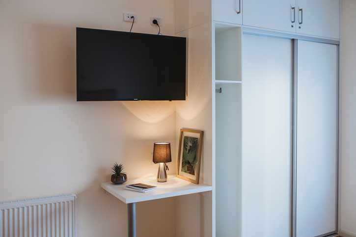 Doutta Galla Harmony Village aged care - closet, desk and mounted television in typical room