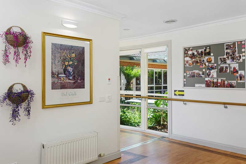 Doutta Galla Woornack - hallway with hanging plants, dooors to outside and paintings