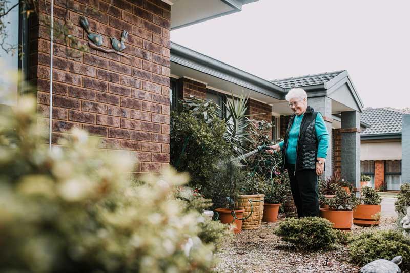 Doutta Galla Harmony Village retirement - senior woman watering garden