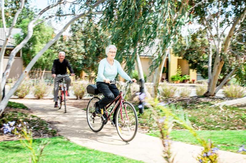 Doutta Galla Harmony Village retirement - senior couple riding bikes in Queens Park
